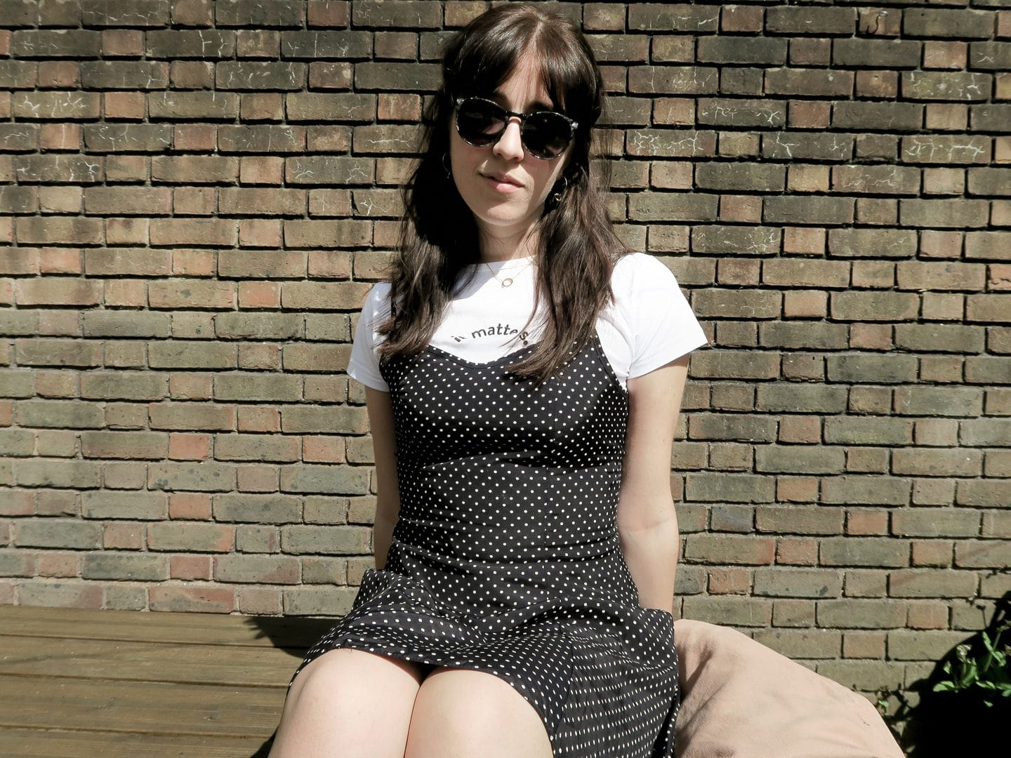 Besma sitting on outdoor table wearing sunglasses, white t-shirt and black dotted dress