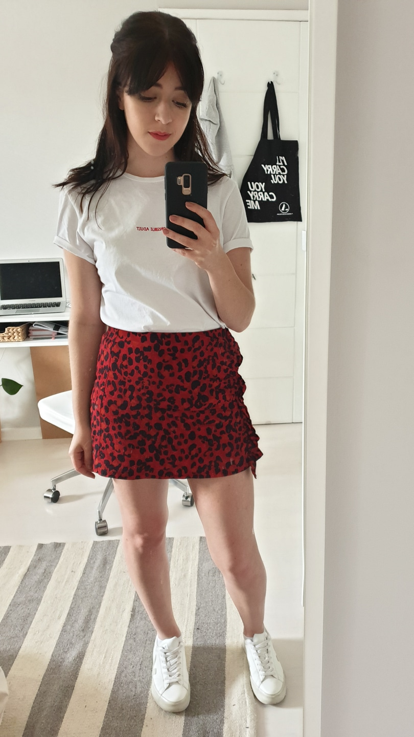 Besma in white Responsible Adult t-shirt with red leopard print skirt