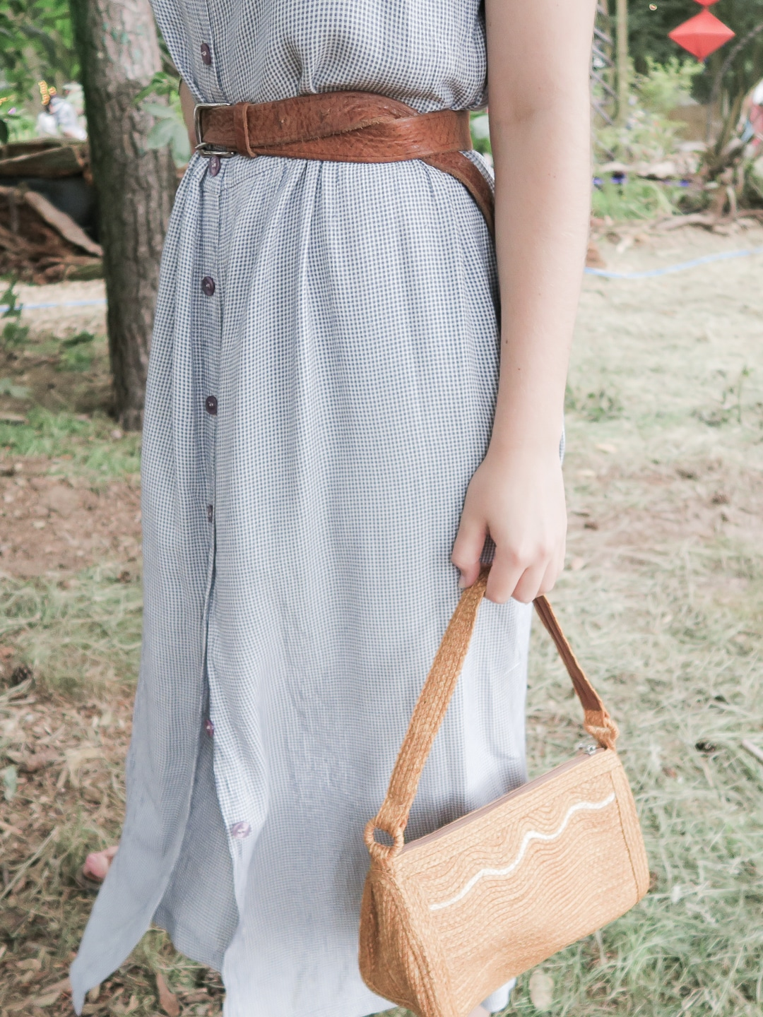 Woman in a blue dress holding a straw bag