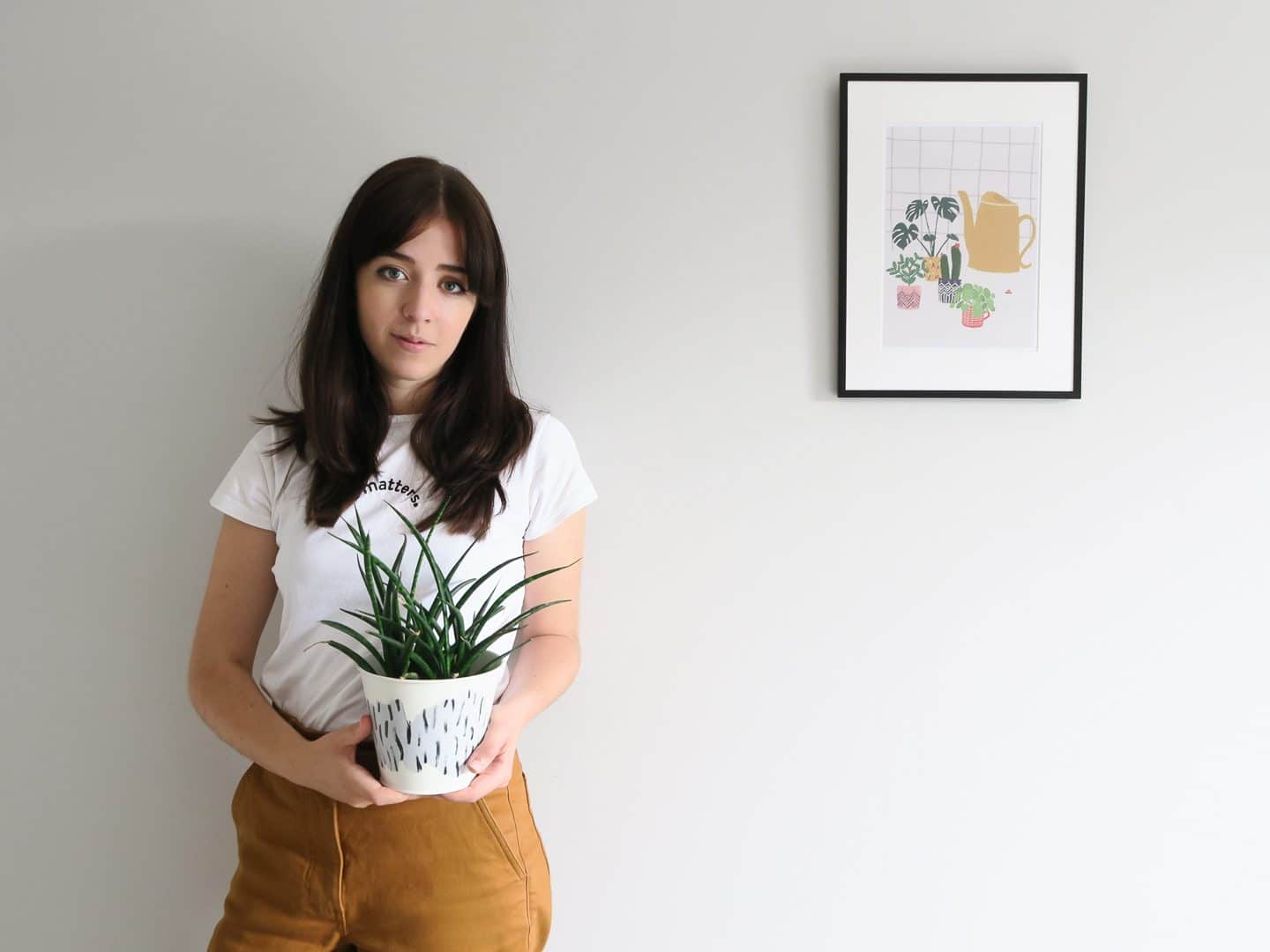 Besma holding a painted plant pot next to a poster
