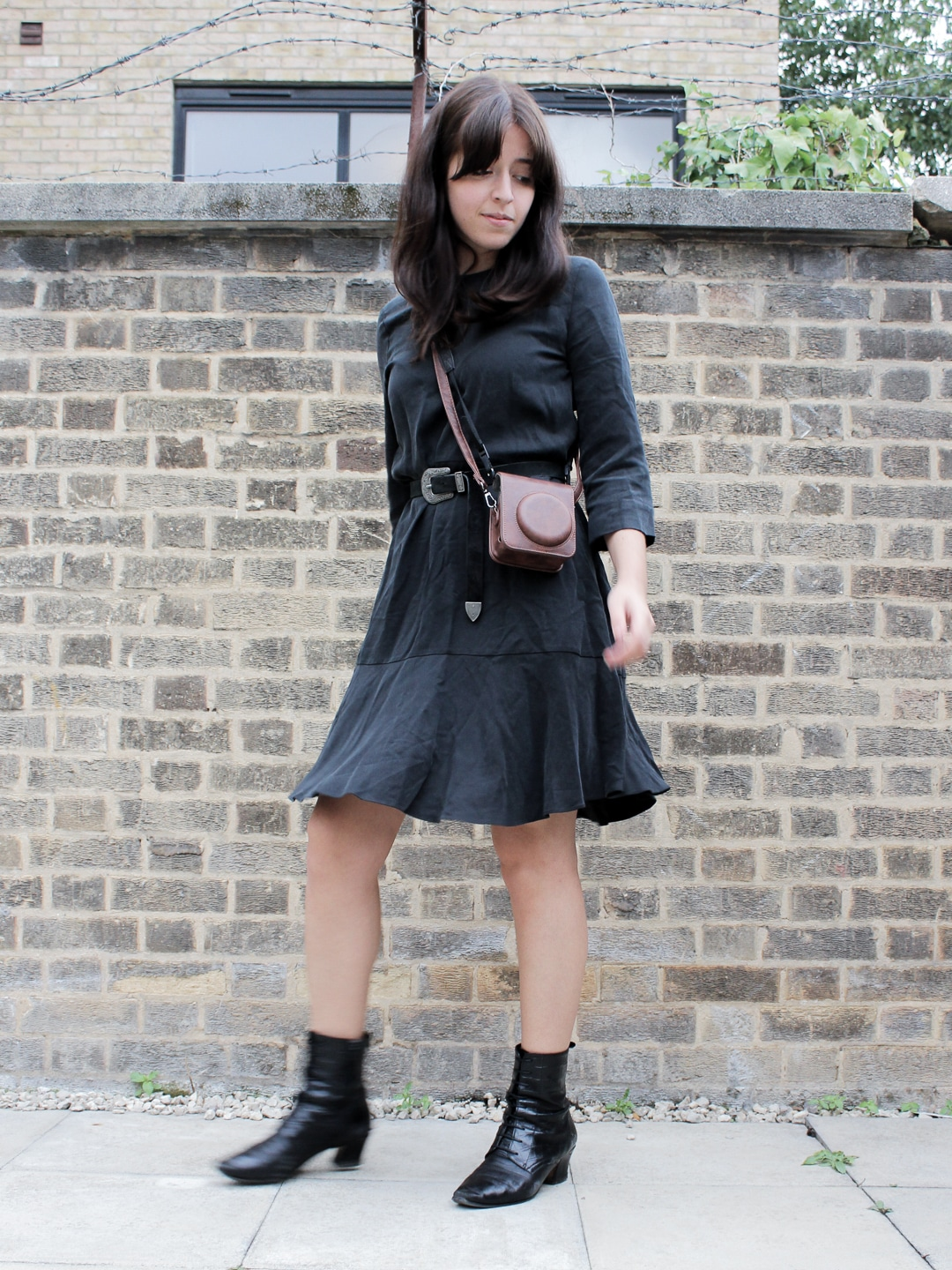 Besma in a black dress with belt, boots, and brown camera bag