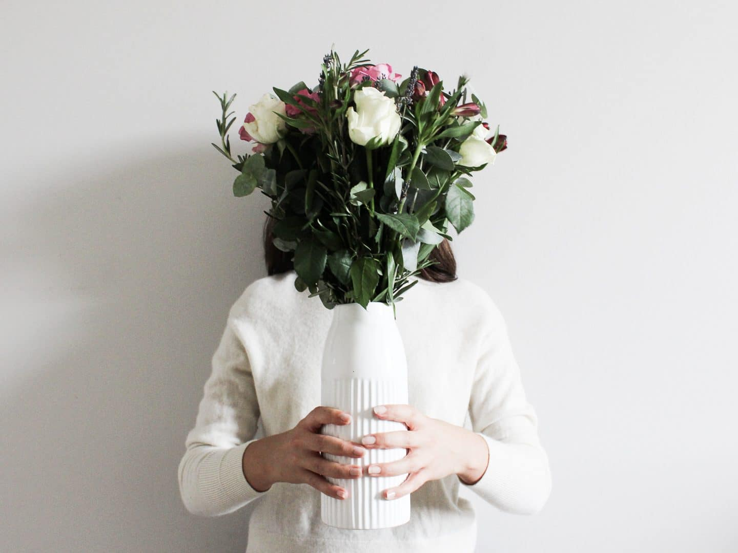 Besma holds a bouquet in front of her face