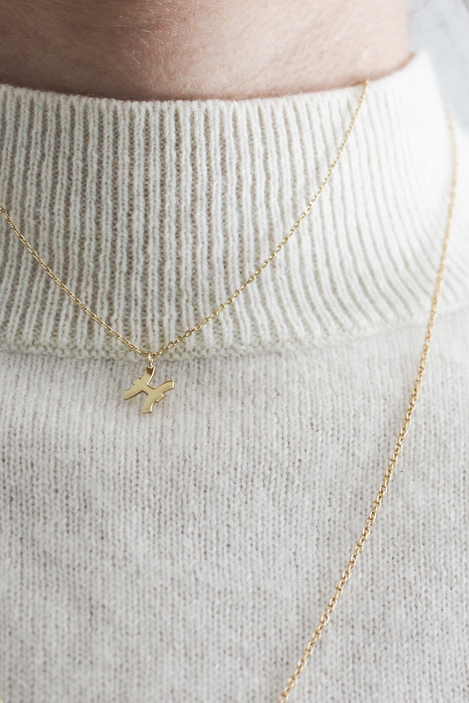 Ethical gold necklaces layered over cream jumper