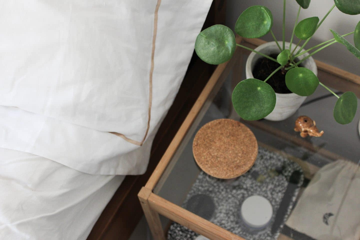 Pillow next to bedside table decorated with plant and cork coaster