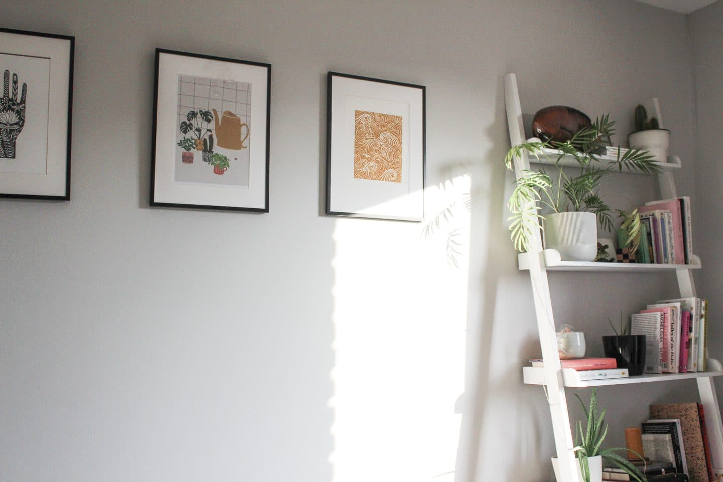 Three picture frames next to a ladder bookcase