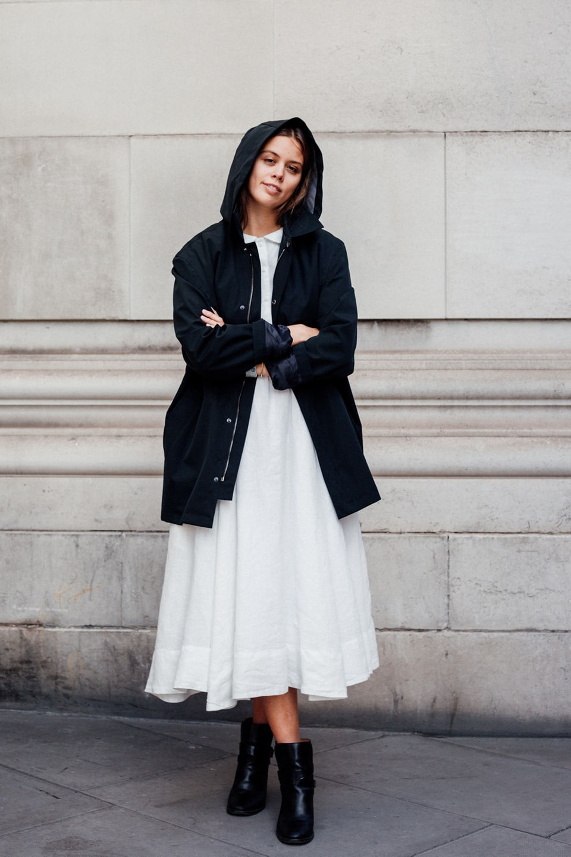 Jil wears white dress with black hooded coat
