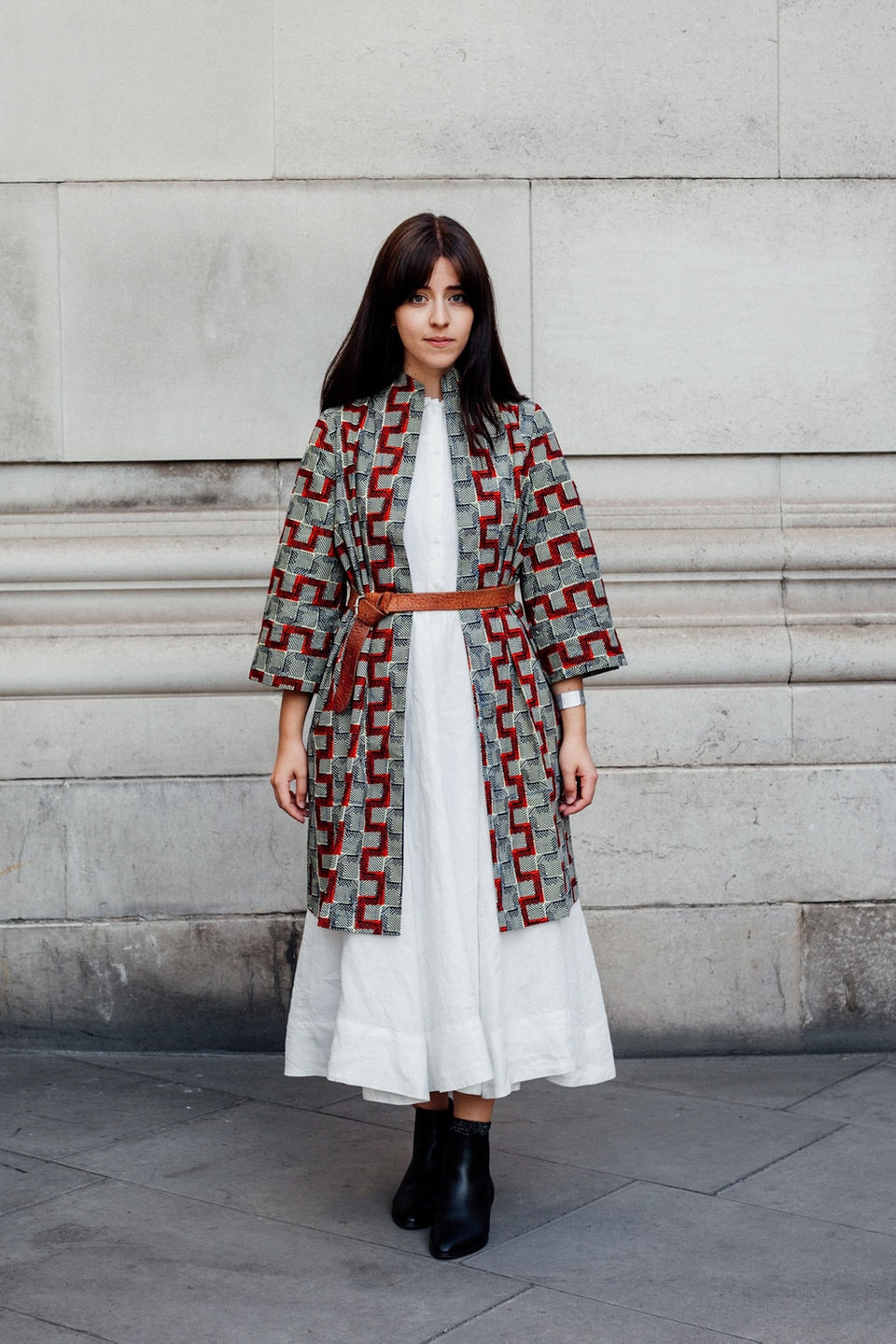 Besma wears white dress with printed longline jacket and belt