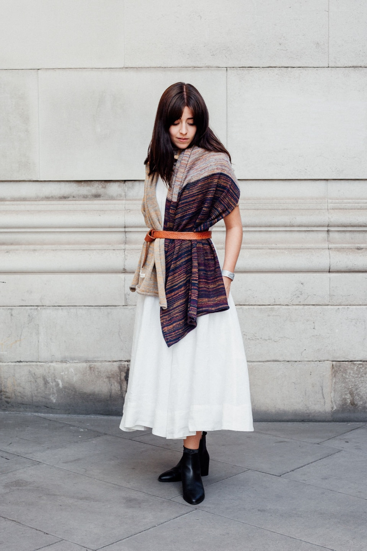 Besma wears white dress with decorative shawl and belt