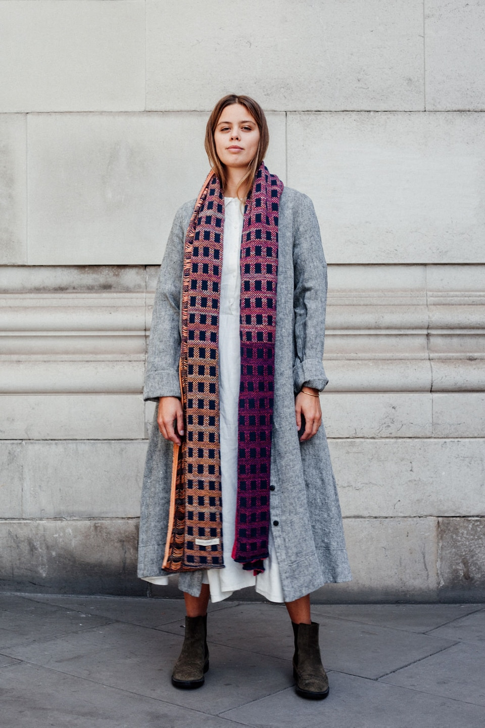 Jil wears white dress with grey jacket and long knitted scarf