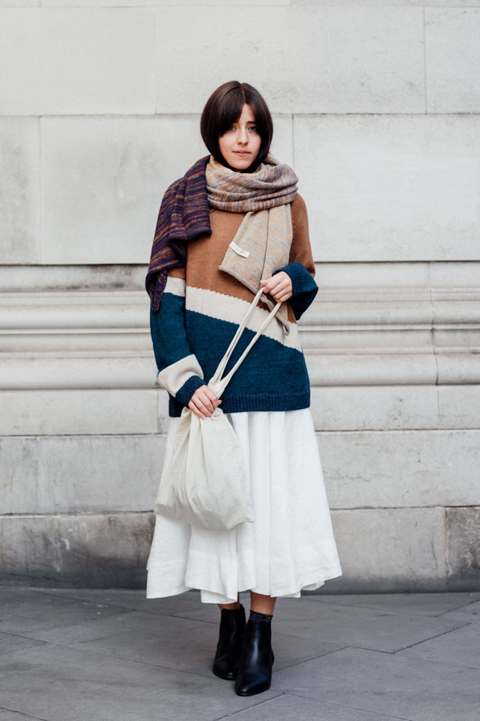 Besma wears white dress with multi jumper, scarf, and tote bag
