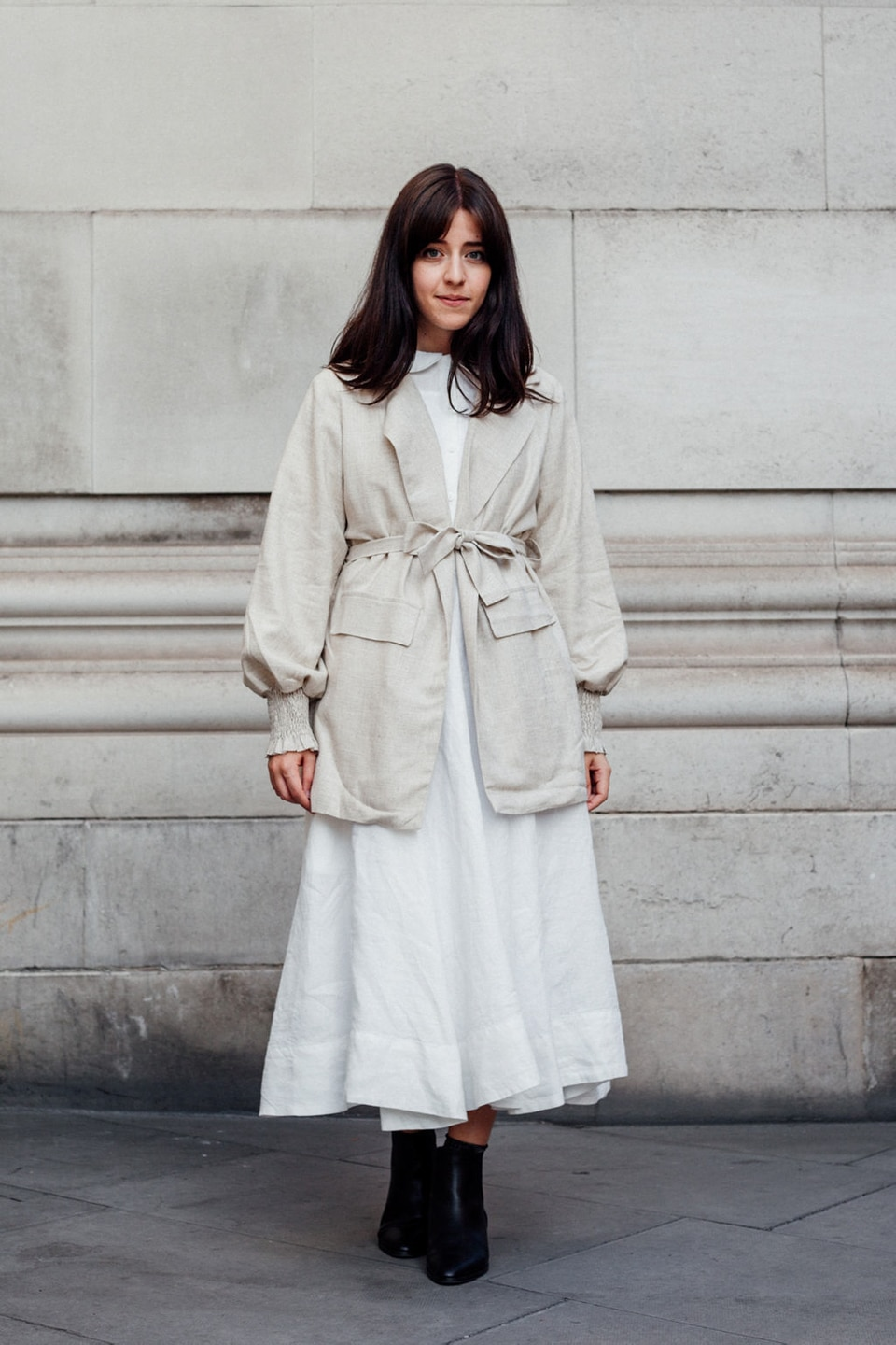 Besma wears white dress with cream linen jacket