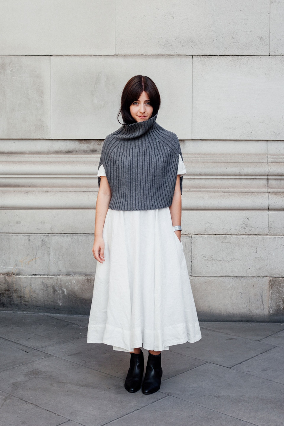 Besma wears white dress with grey pullover