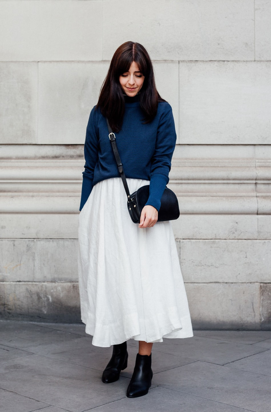 Besma wears white dress with blue jumper and bag