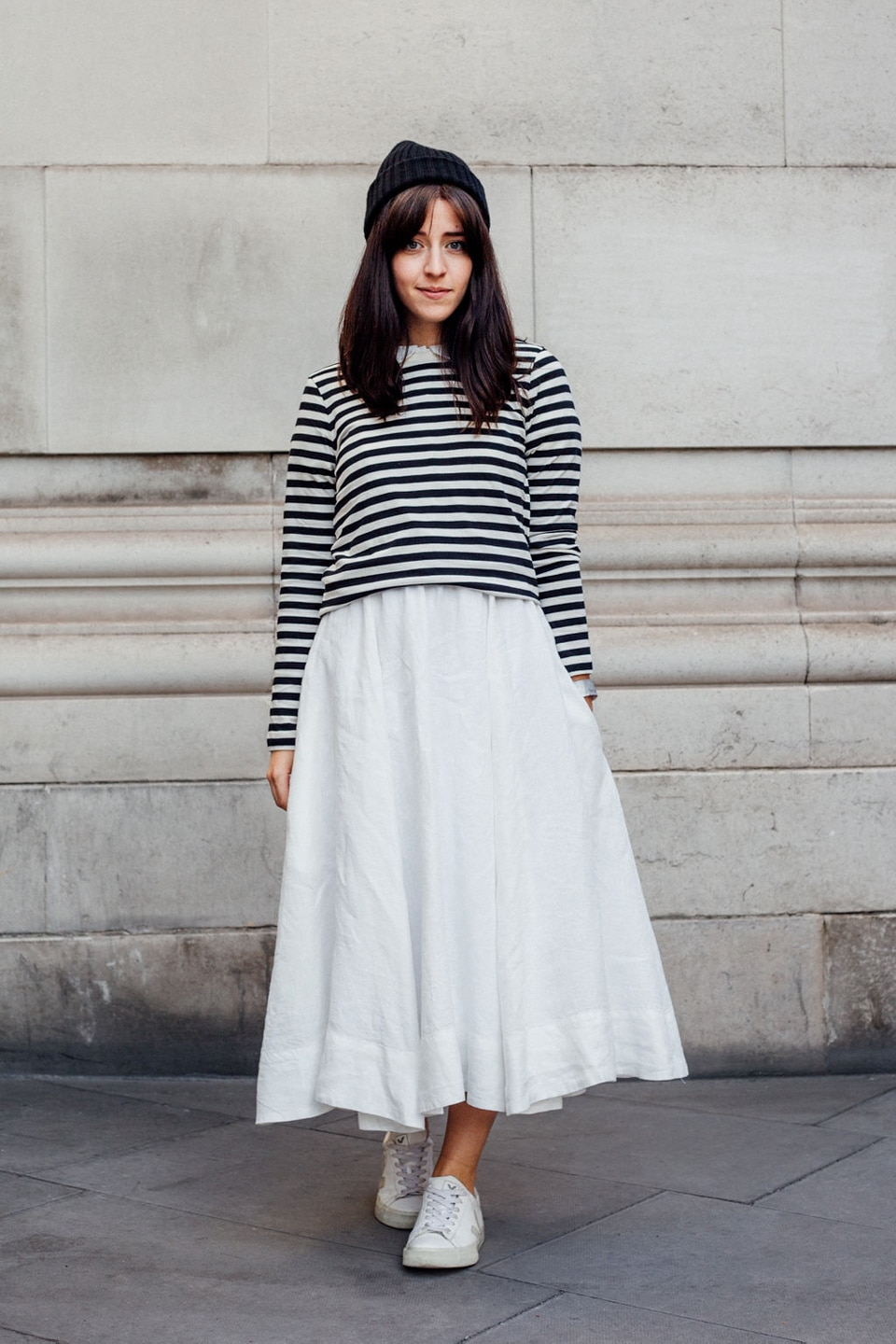 Besma wears white dress with striped pullover