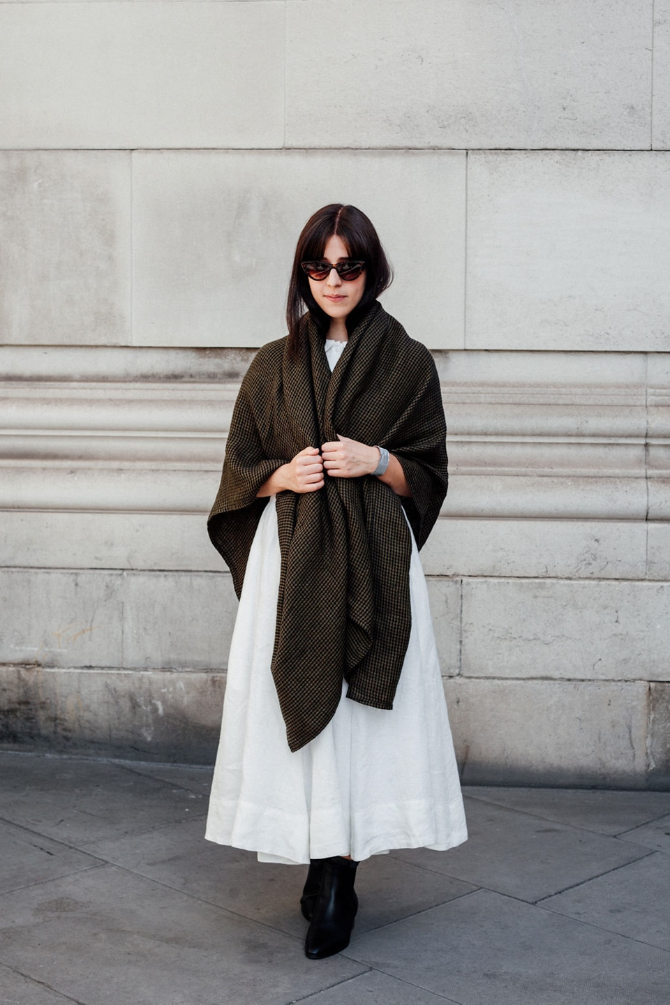 Besma wears white dress with brown shawl and sunglasses