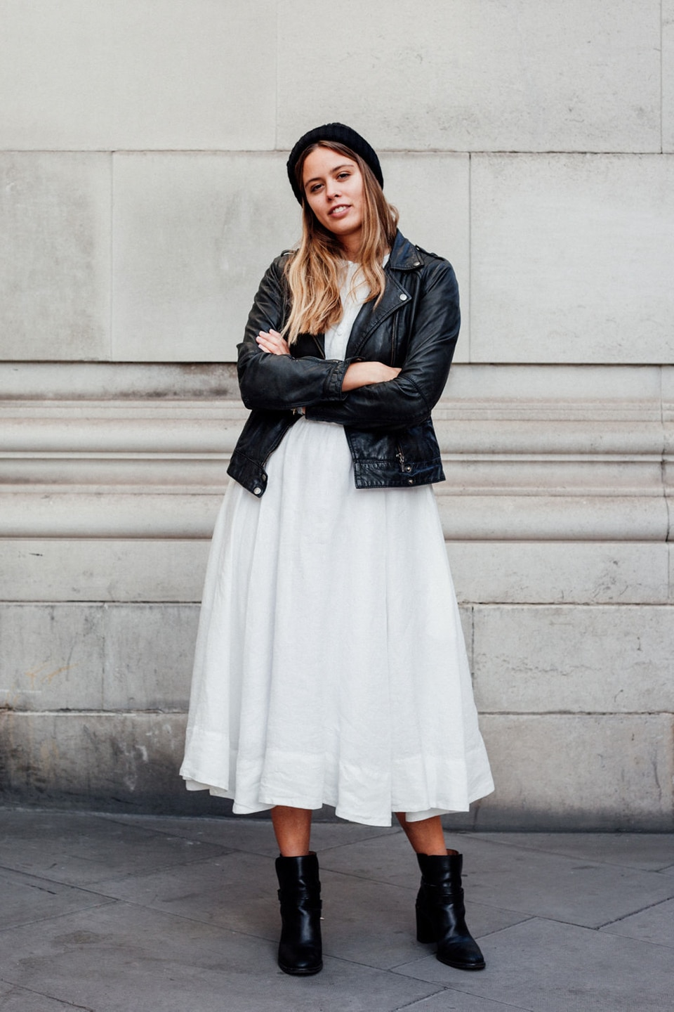 Jil wears a white dress with black leather jacket and hat