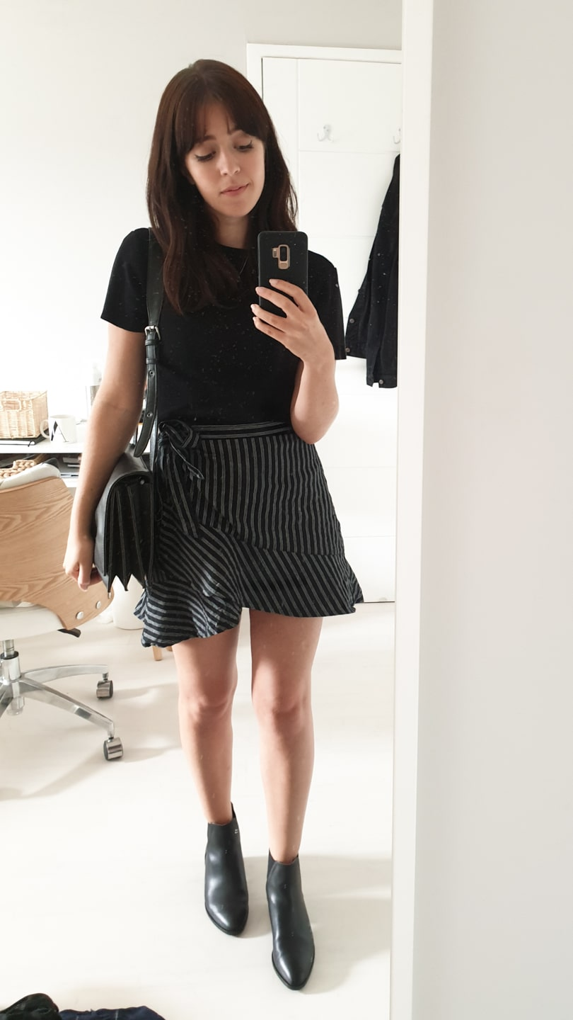 Black short-sleeved jumper with striped mini skirt and black boots