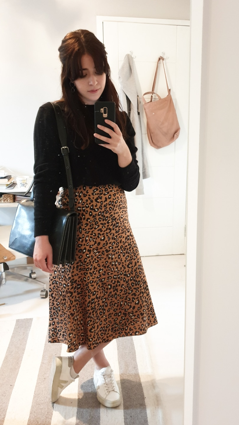 Black long-sleeve jumper with leopard print skirt and white sneakers