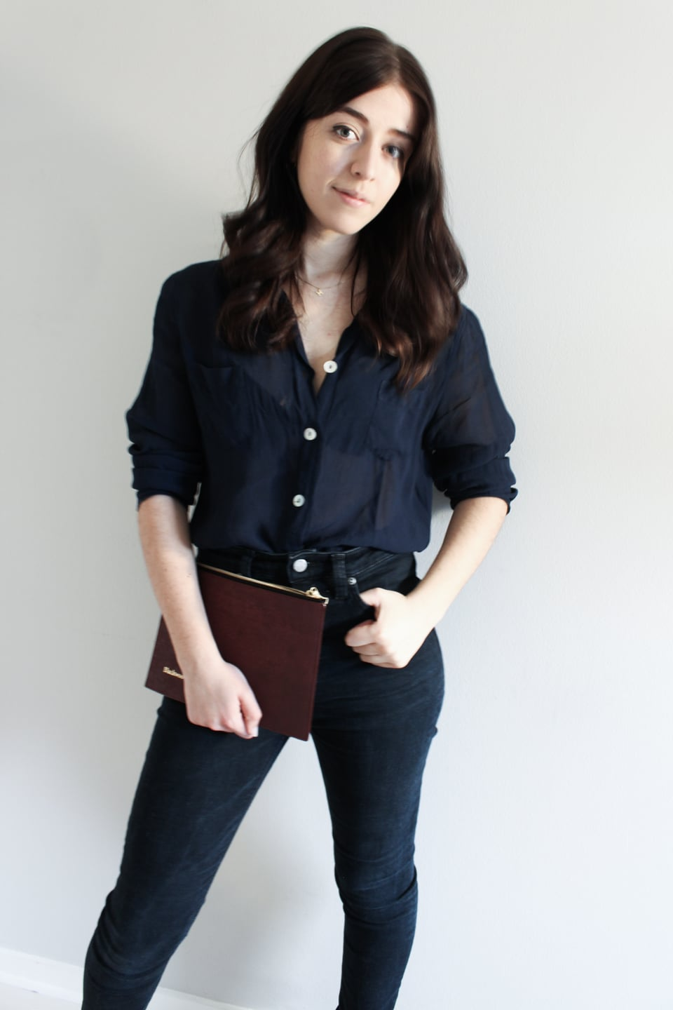 Besma wears second-hand top, sustainable Nudie jeans, vegan leather clutch