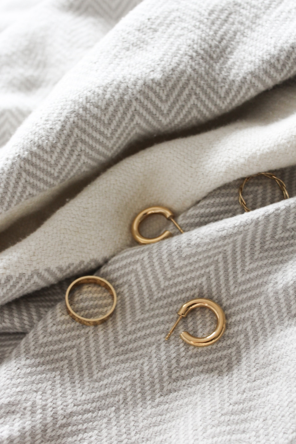 Gold rings and earrings scattered on a blanket