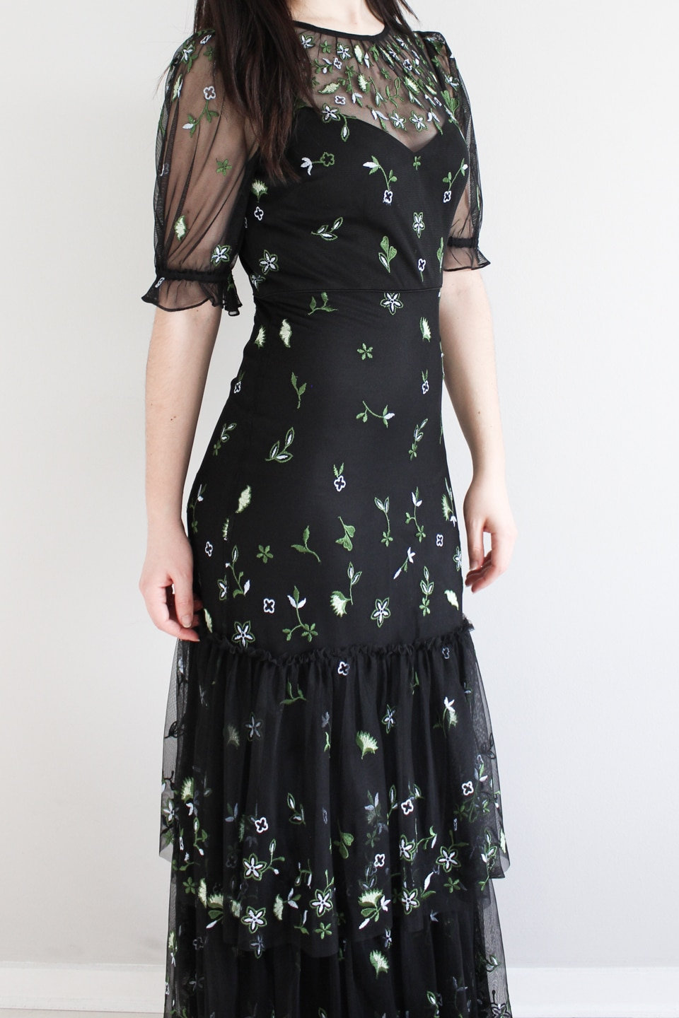 Close up of black dress with embroidered flowers