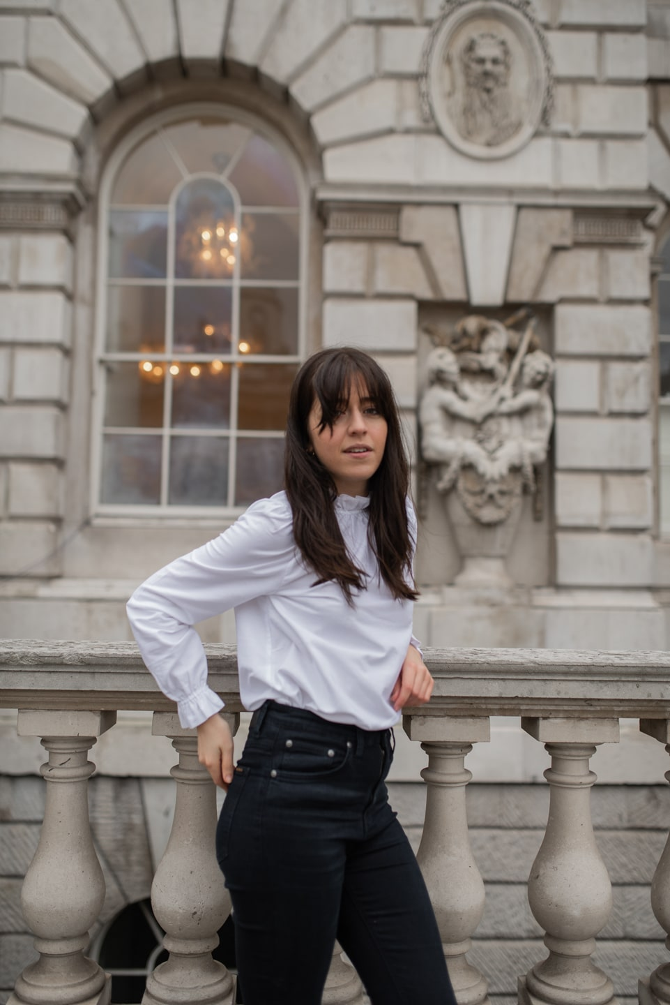 Besma wears Sezane organic cotton blouse and dark blue jeans