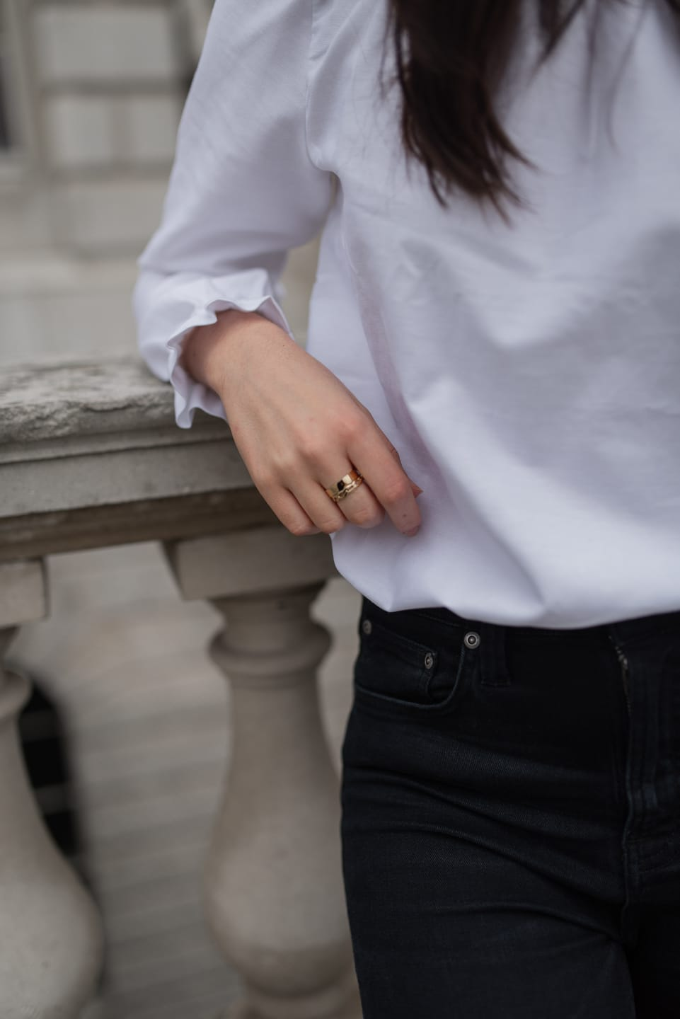 Close up of Sezane white blouse, rings, and jeans