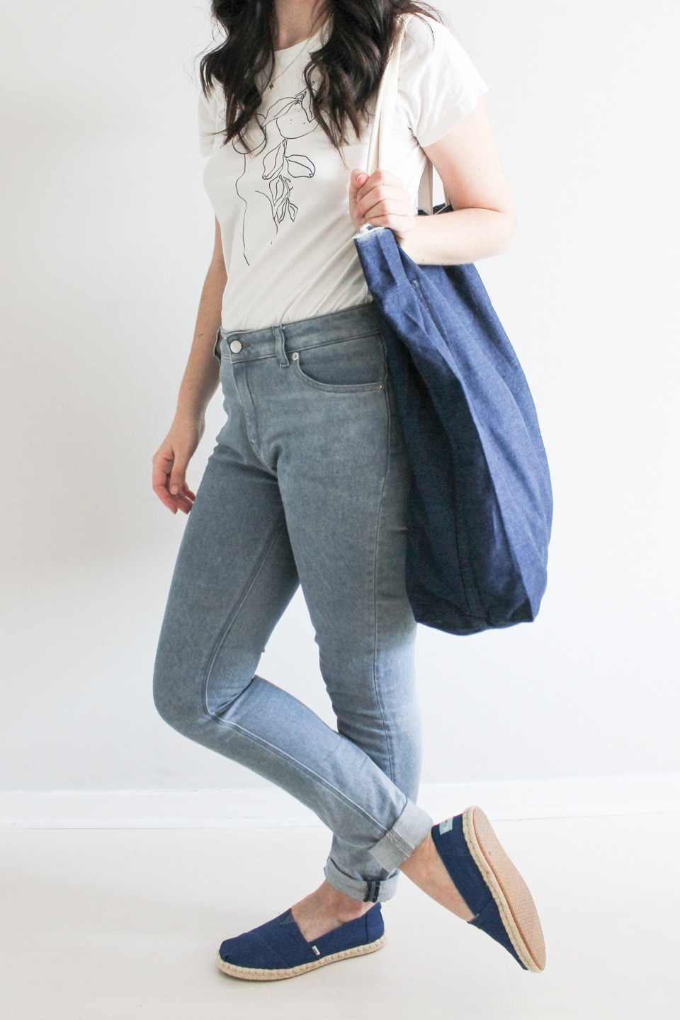 Blue TOMS Shoes styled with white t-shirt, jeans, and denim tote bag