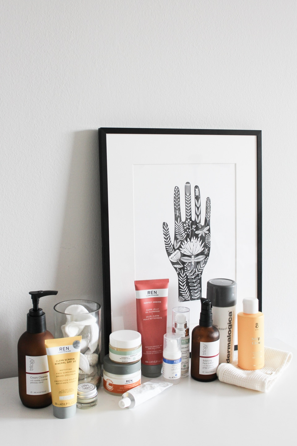 Skincare products next to a framed print