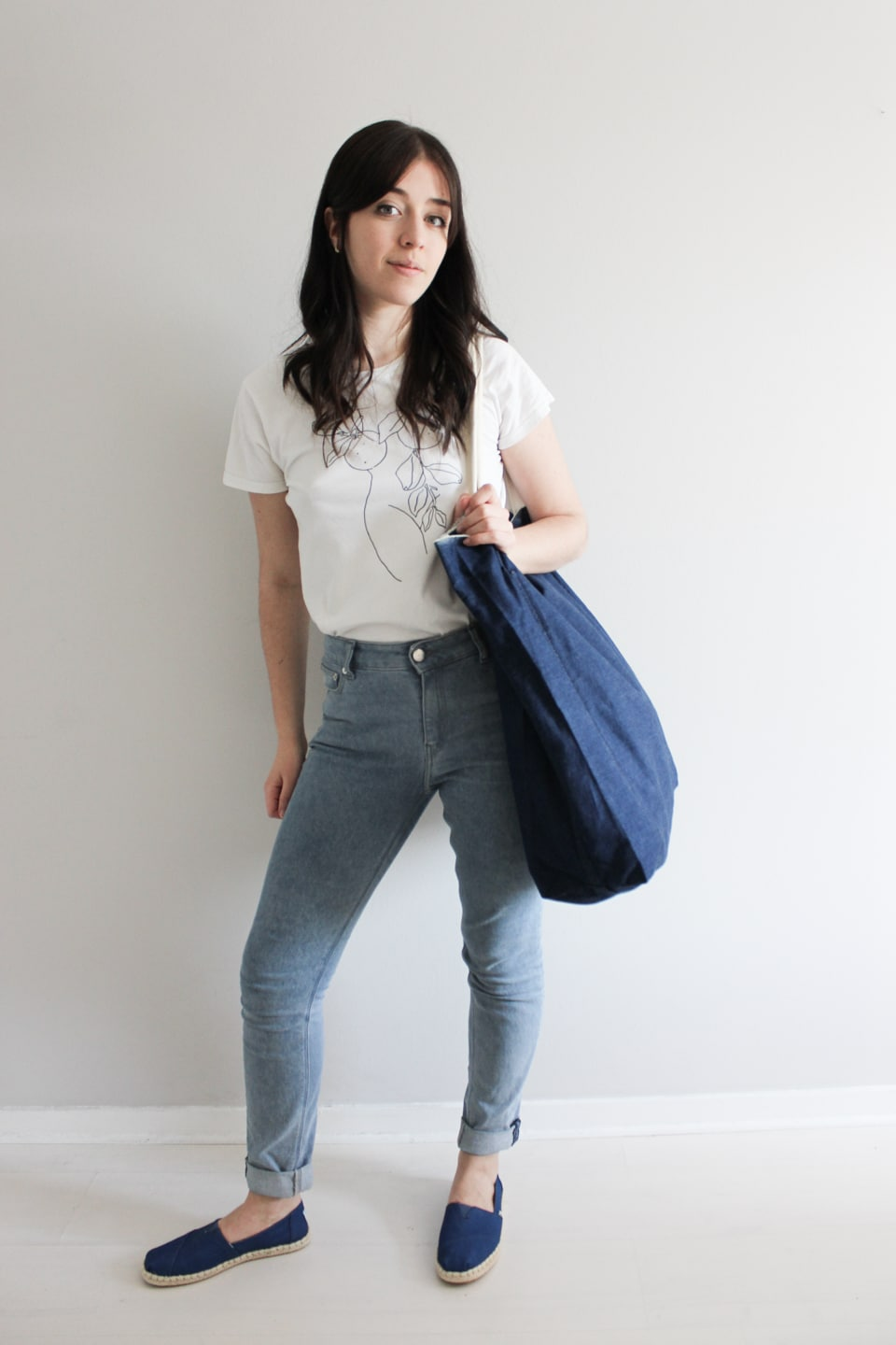 Besma wears white t-shirt, blue jeans, and blue TOMS EarthWise flat shoes