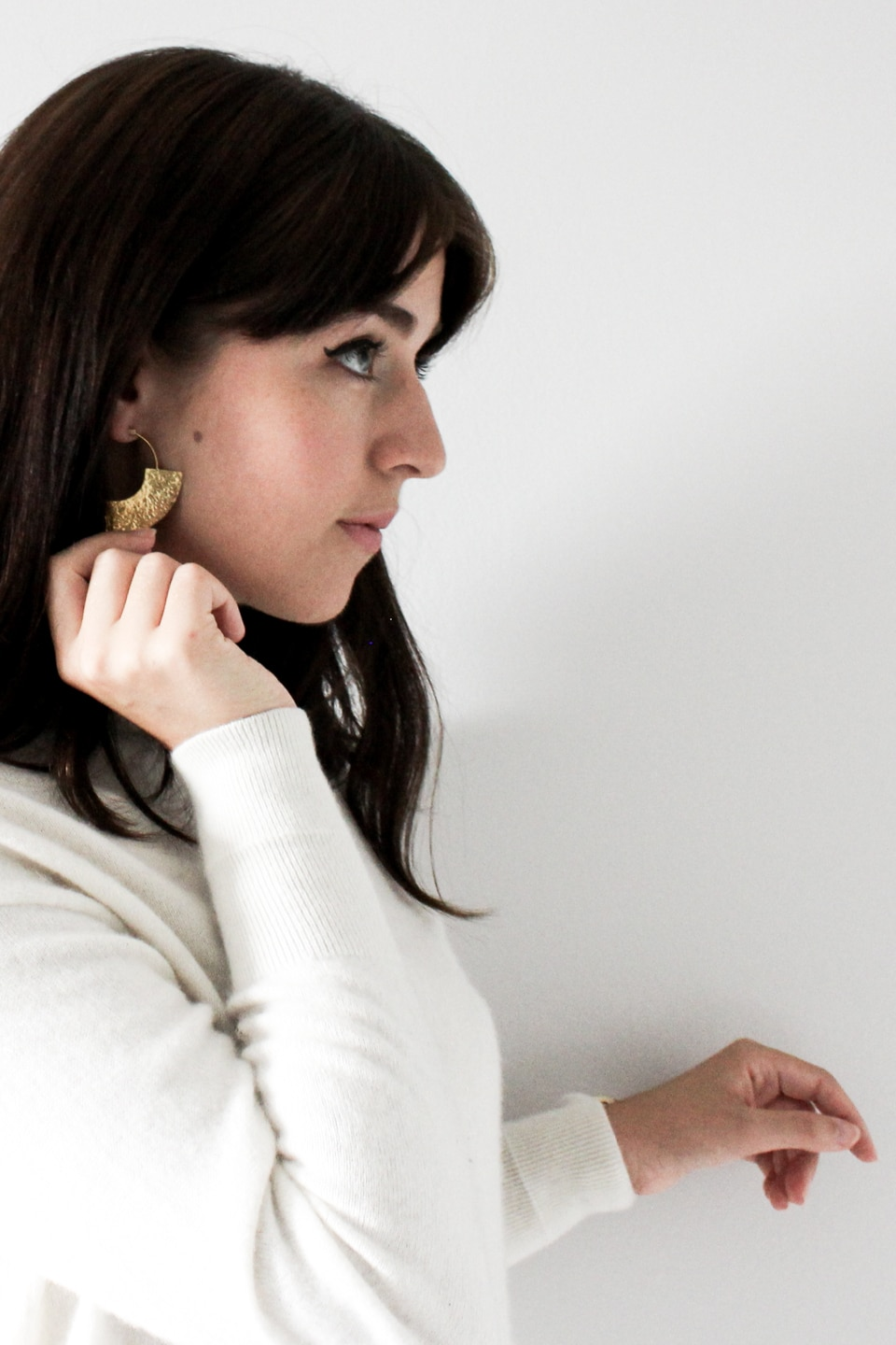 Besma wears large brass earring from Yala Jewellery