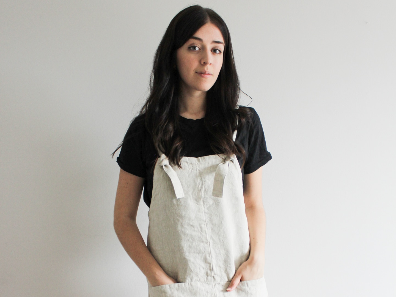 Besma wears black t-shirt and cream linen romper