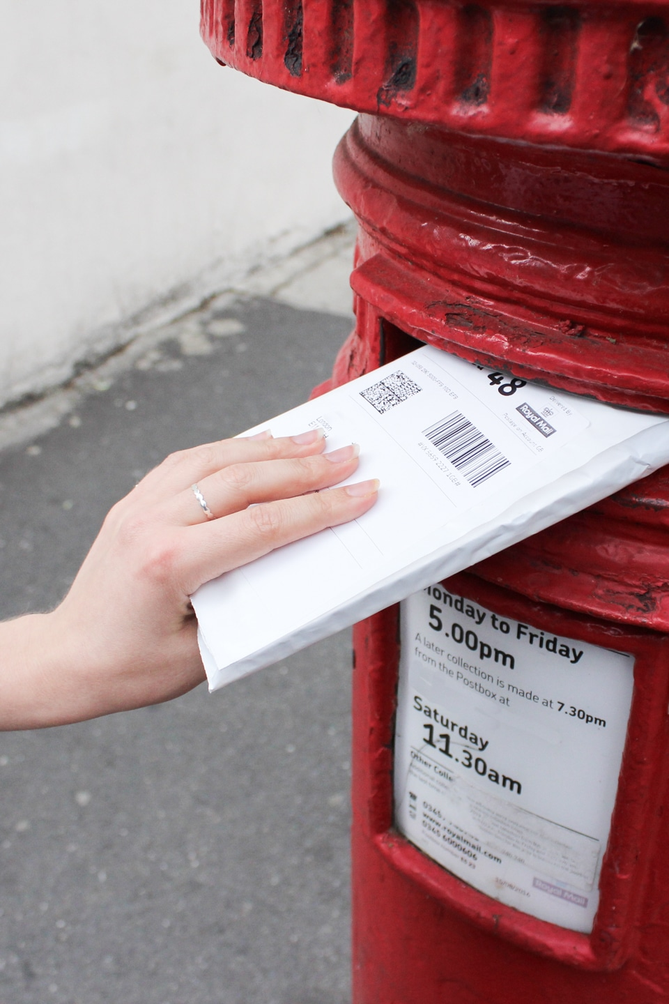 Envelope containing phones going into red postbox