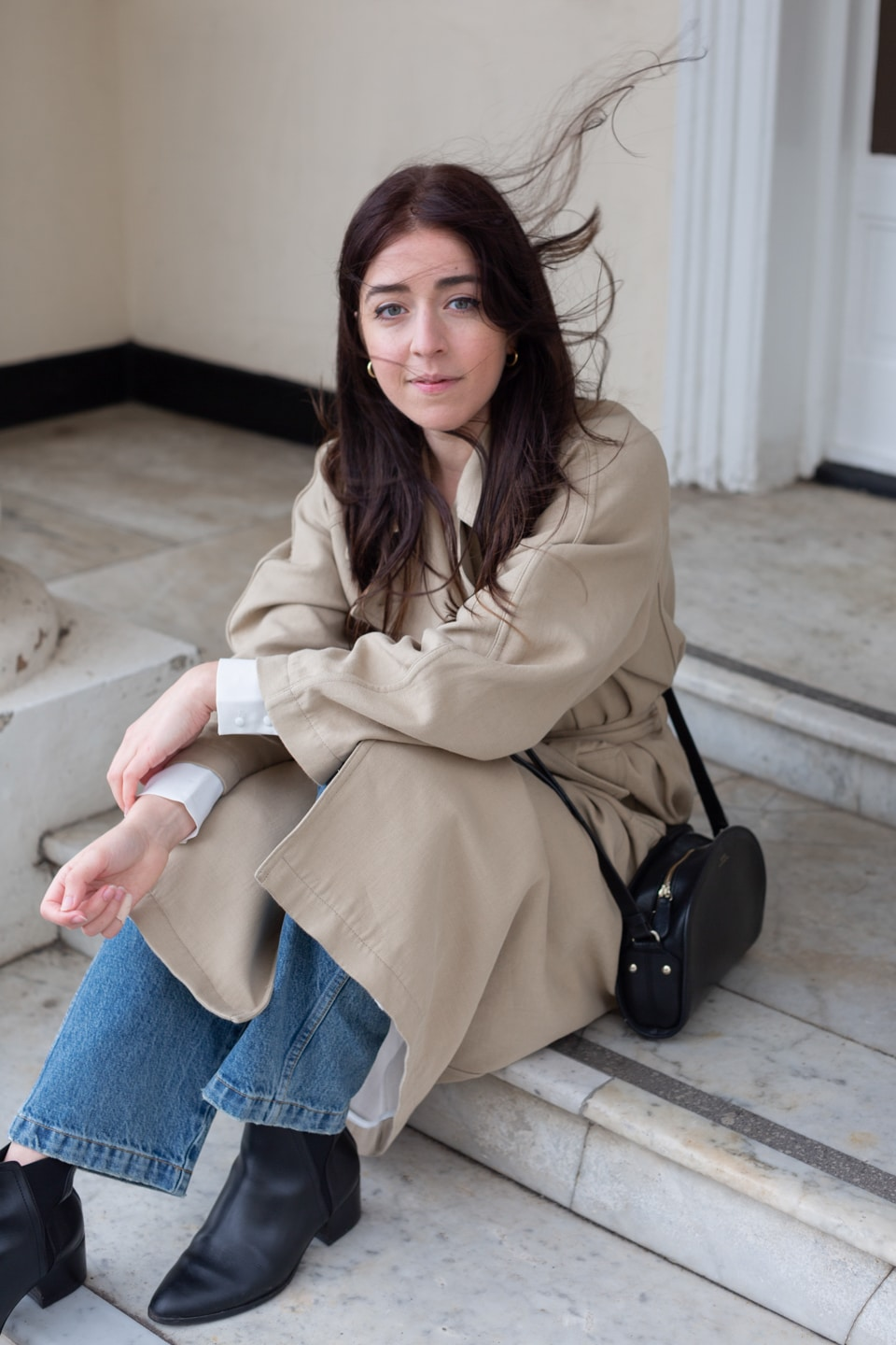 Besma smiling wearing trench coat, crossbody bag, jeans, boots