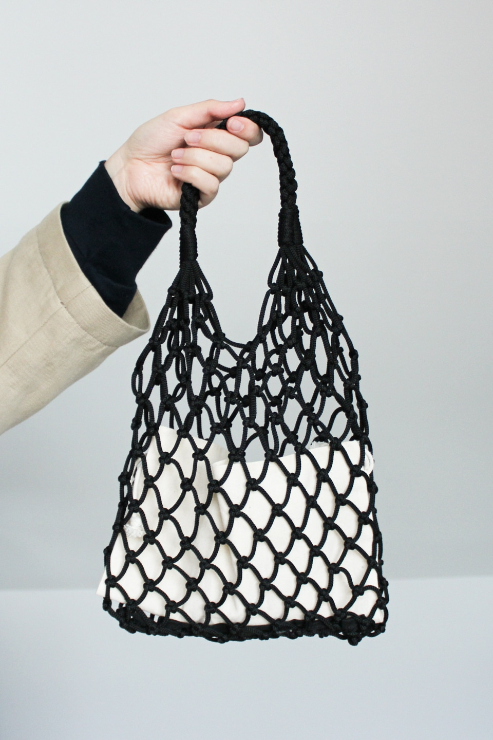 Hand holding up black knotted bag