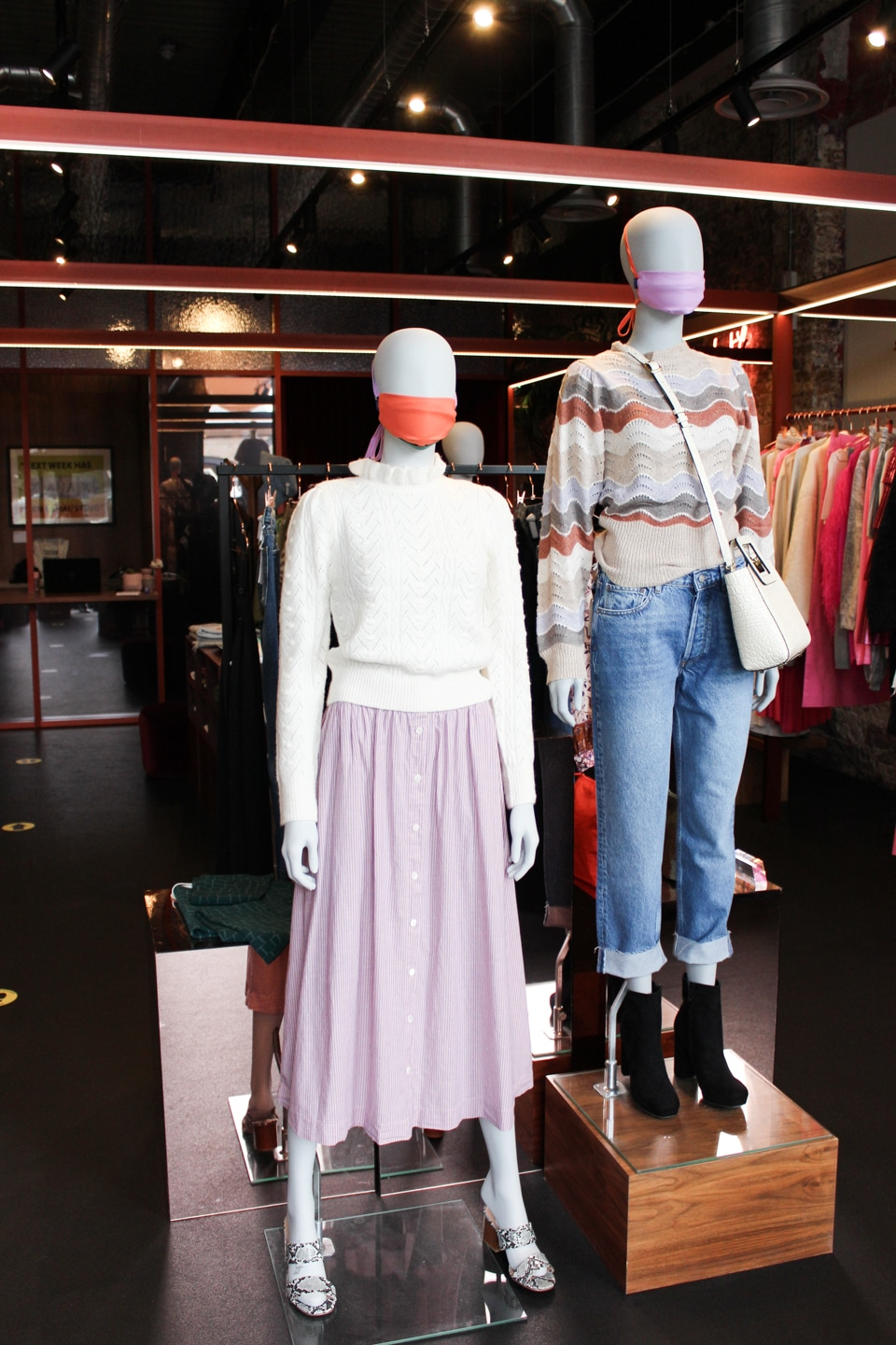 Two mannequins wearing masks and clothes at Twiin Store