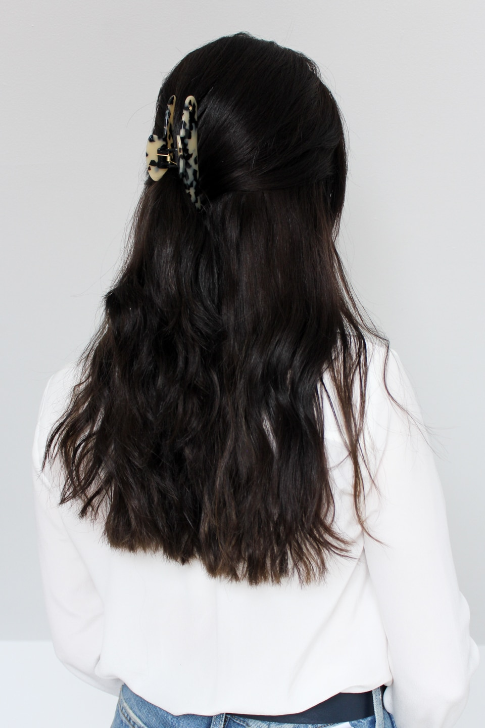 Back of woman's head with hair down and held with clip