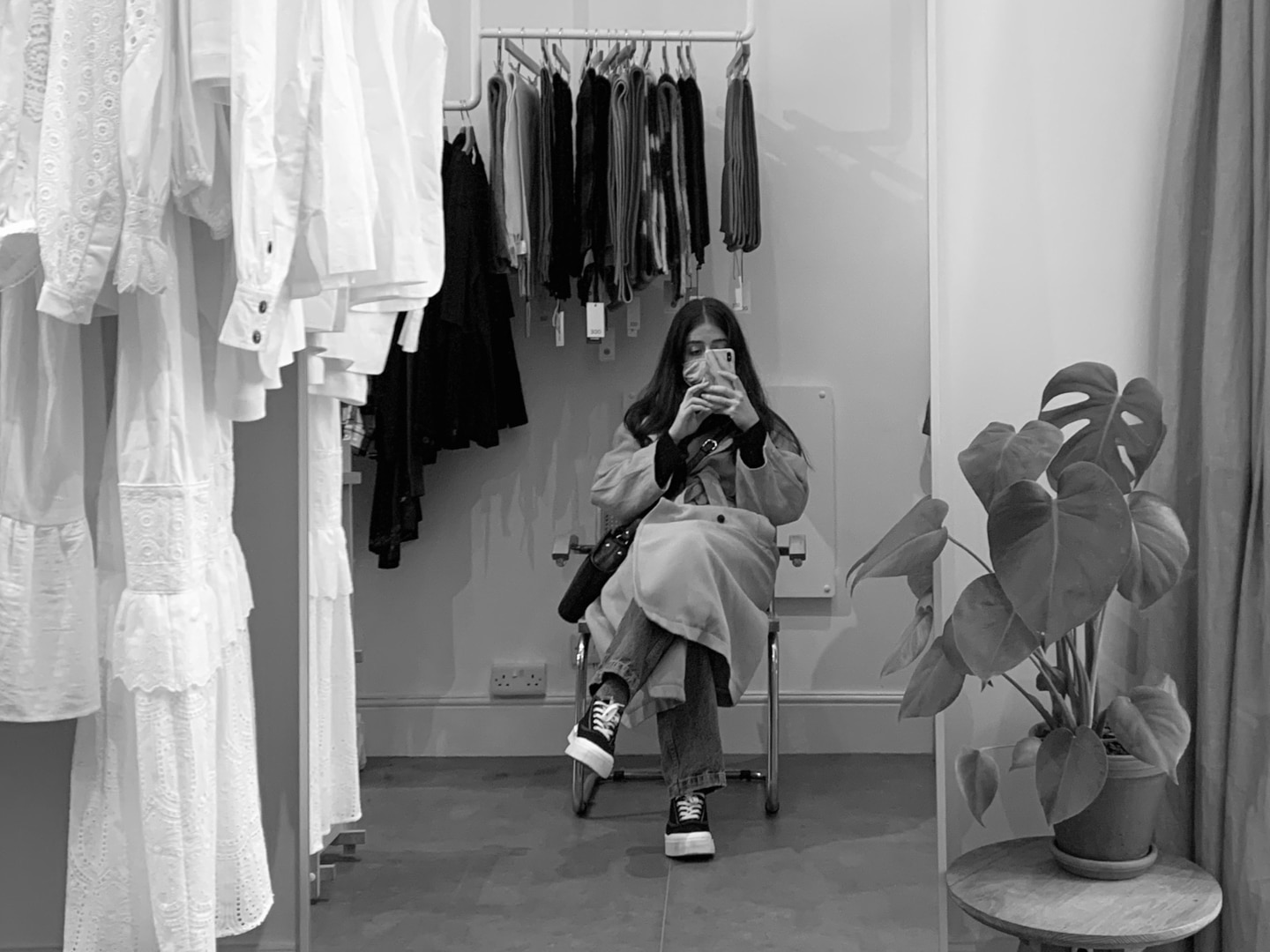 Besma takes a selfie in a shop mirror. Photo is in black and white.