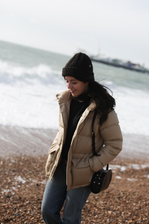 Besma walks along Brighton pebble beach wearing a parka, hat, and jeans