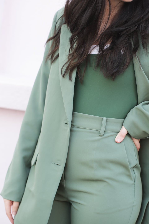 Besma wears Econyl swimsuit with green suit