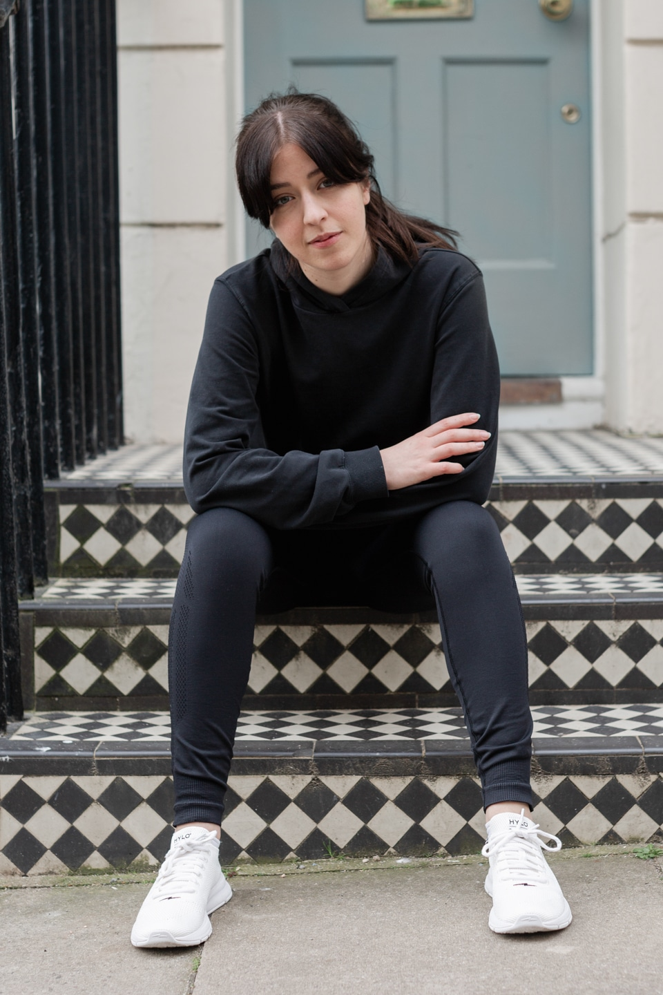 Besma wears black track suit and Hylo sustainable sneakers