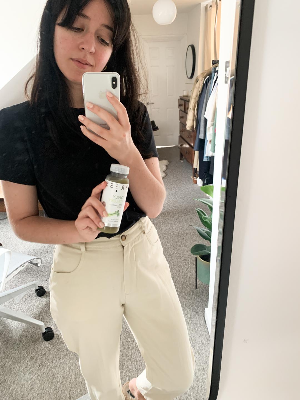 Besma holding PRESS Daily Celery Juice in Mirror Selfie