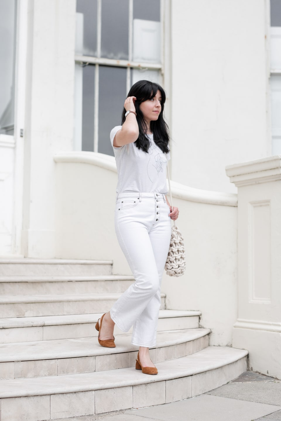 Besma wearing white t-shirt and jeans with Solios Watch