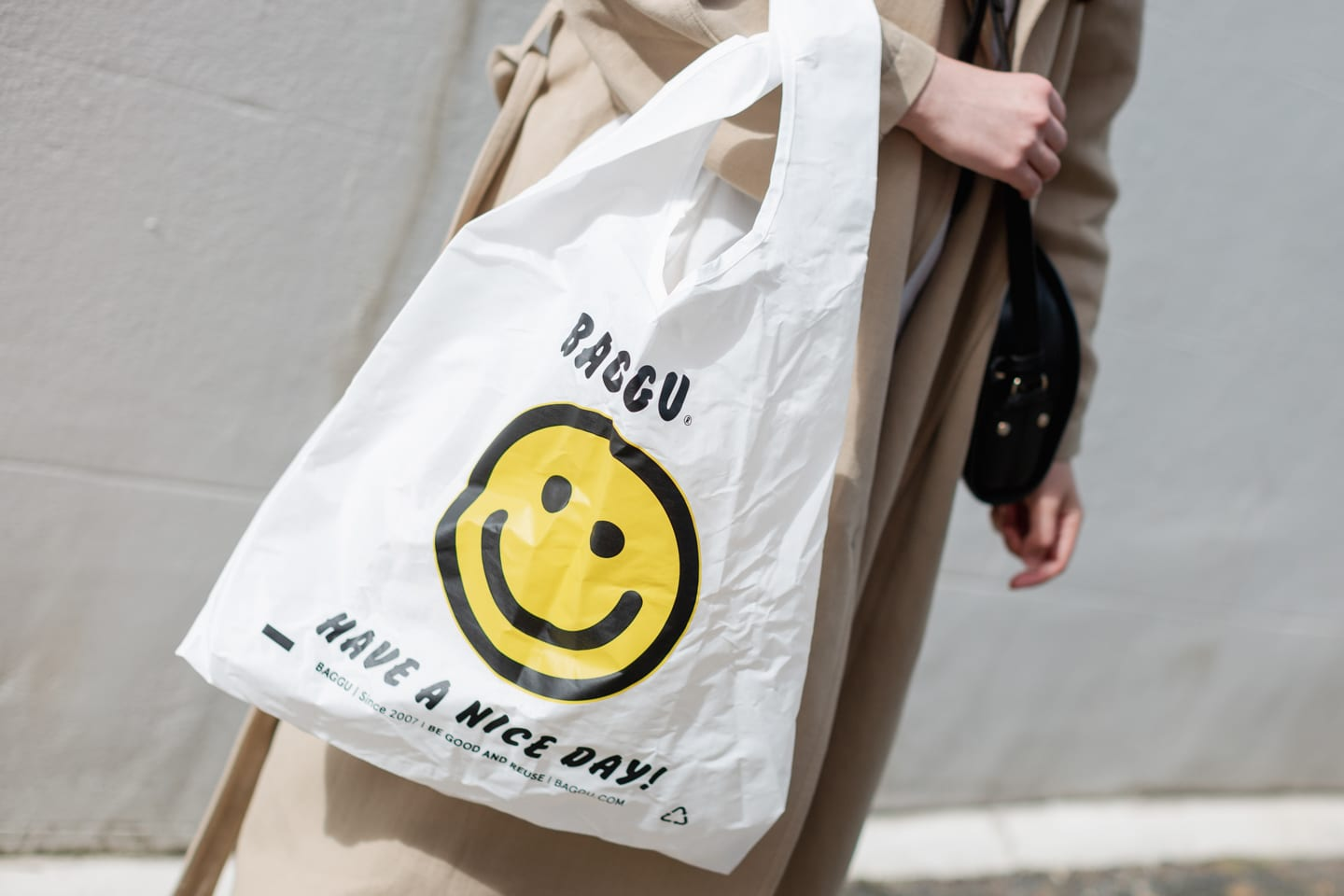 Woman holds reusable tote bag in style of disposable bag
